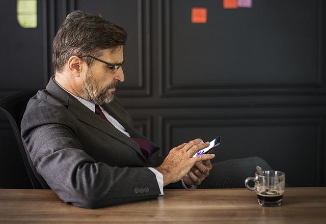 podnikatel s mobilem u kávy.jpg