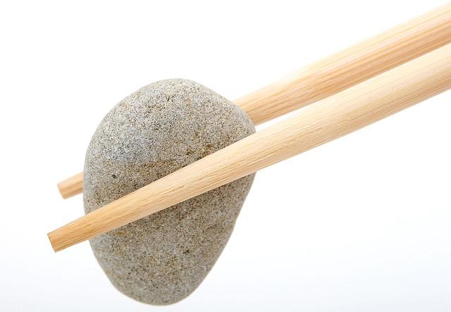 šedý oblázek mezi dřevěnými hůlkami