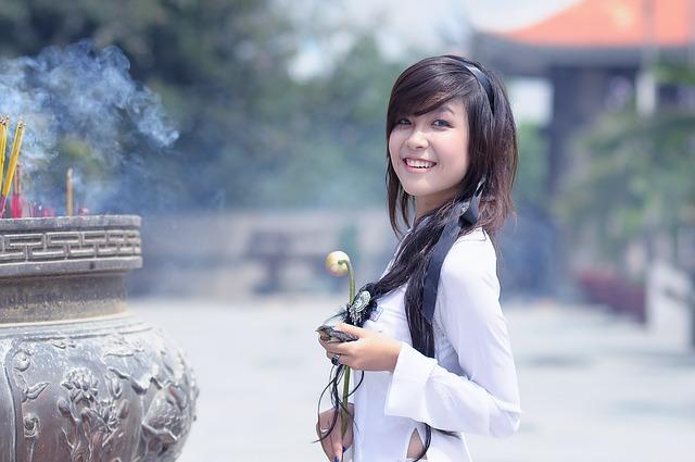 asijská dívka s květinou u kadidel.jpg