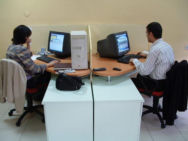 dva experti sedící u počítačů naproti sobě