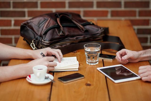 lidé sedí u dřevěného stolu